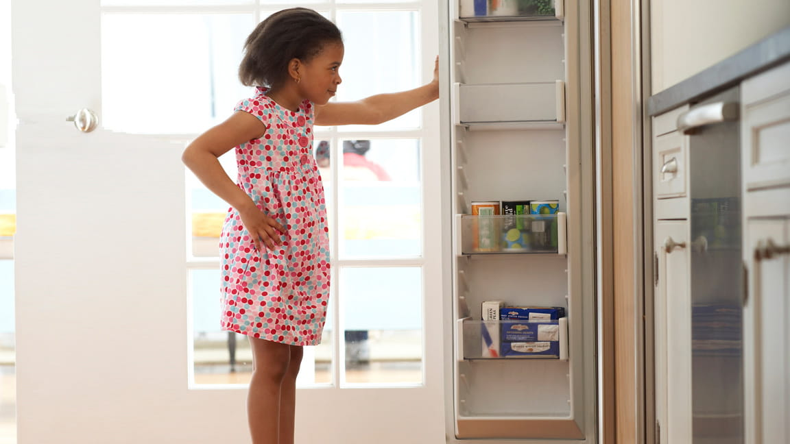 girl looking in kitchen pantry