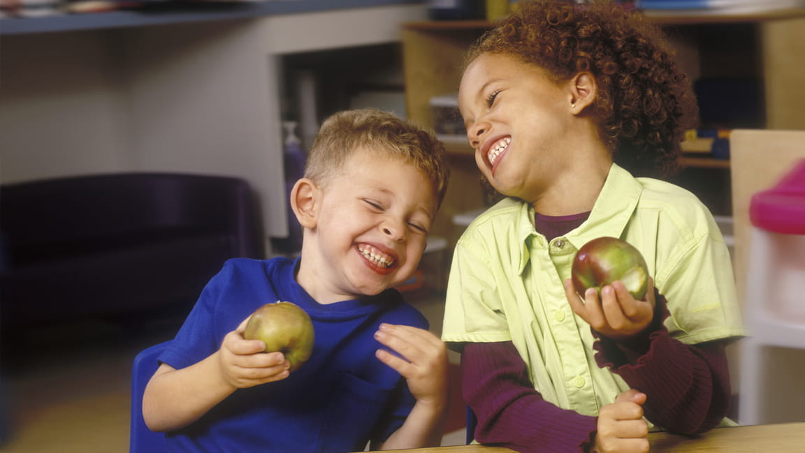 boys laughing while eating apples
