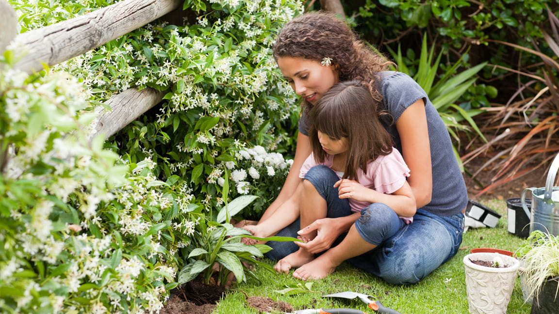 mother and daughter planting in garden