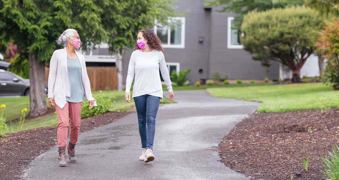 mother and adult daughter walking in neighborhood wearing masks