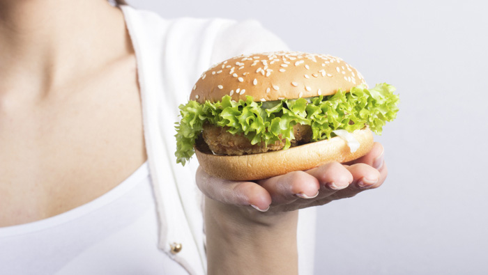 close up of chicken sandwich on a woman's hand