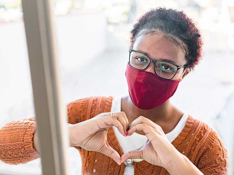 woman wearing mask motioning heart with hands