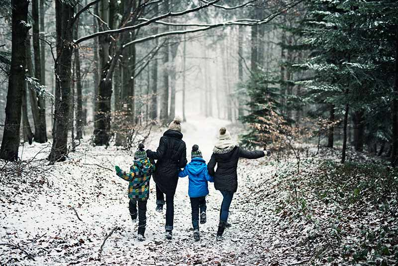 family skips through the forest snow