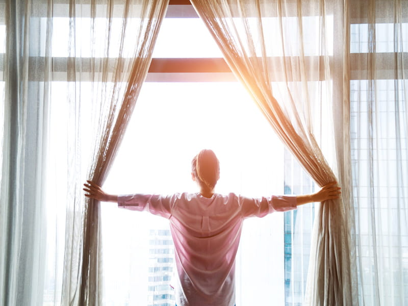 woman opens curtains to sunrise