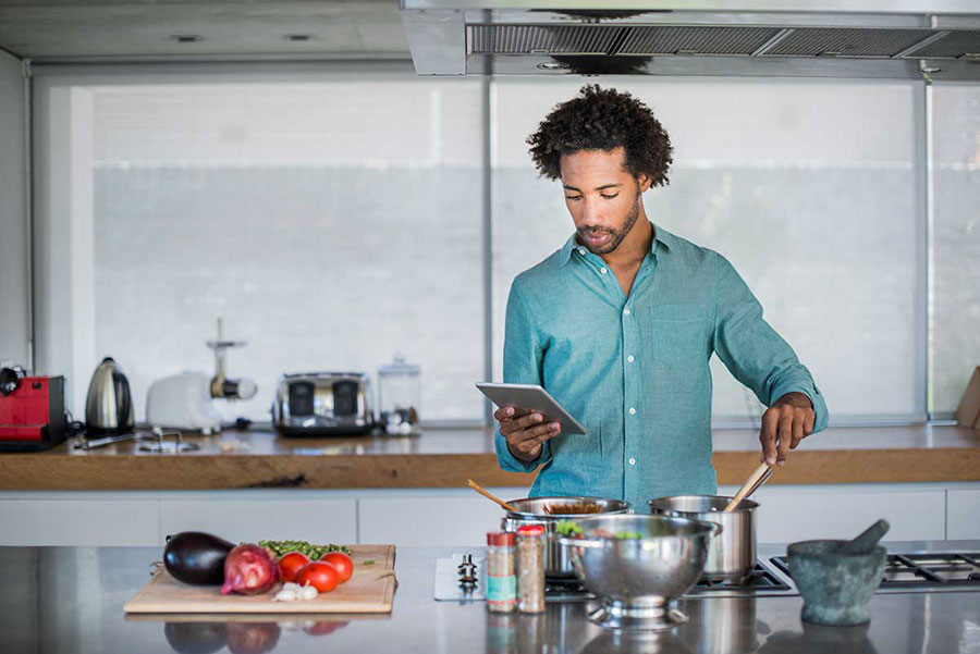 young man reading recipe from tablet while cooking