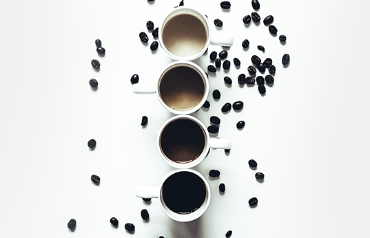 Four cups of coffee on white table with coffee beans scattered around