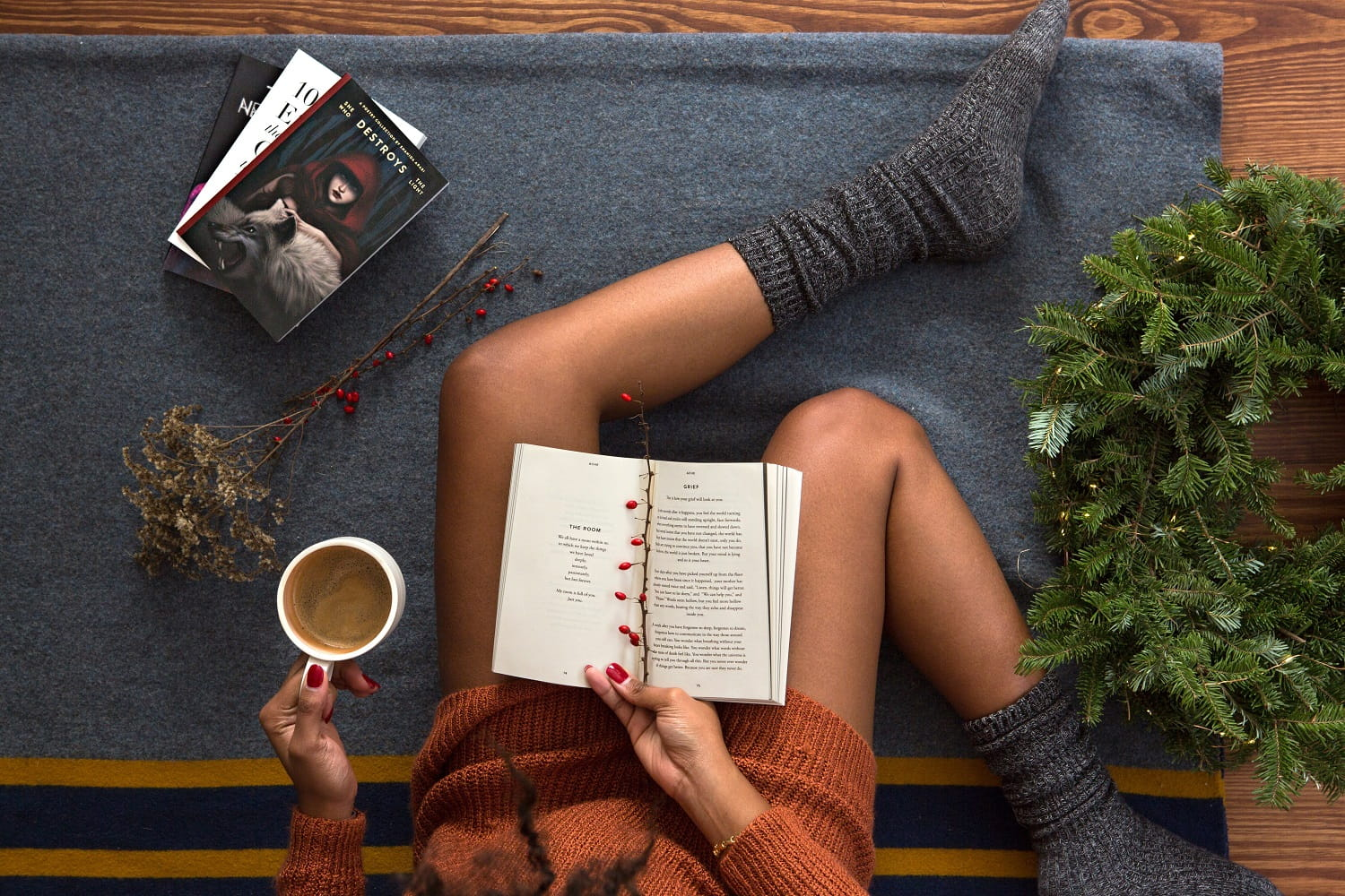 Overhead shot of women in socks reading book with coffee and festive decor
