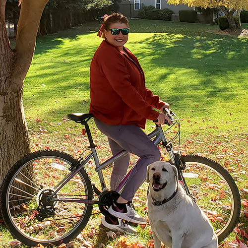 woman on her bike smiling with her dog by her side
