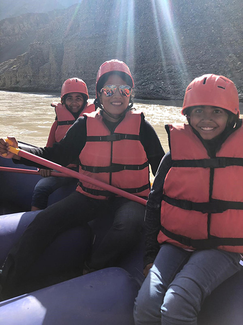Dr. Neelima Vallurupallo and her two kids smiling while water rafting