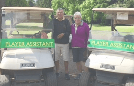"Saving Strokes volunteers standing near golf carts that read ""player assistant"""