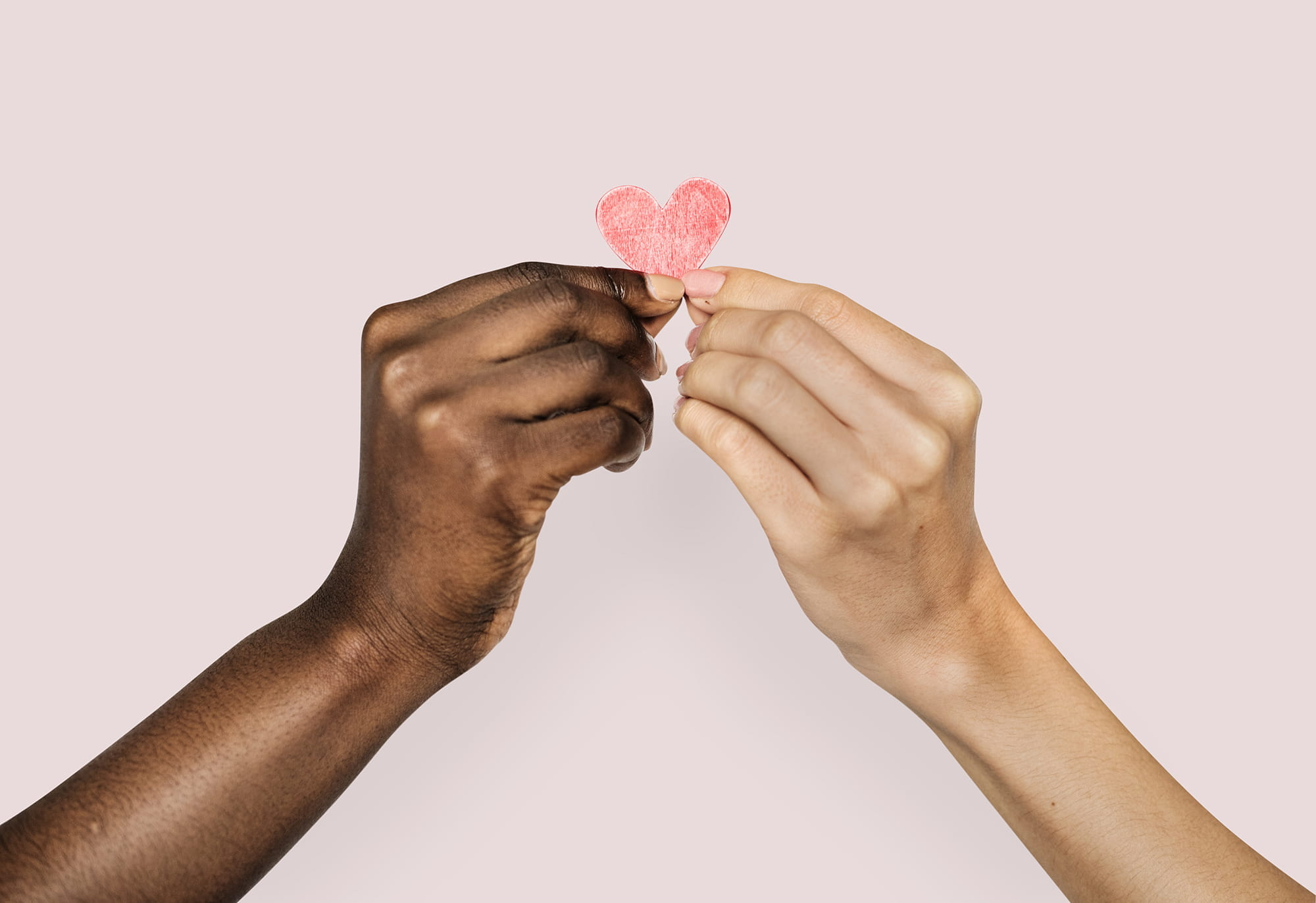 Two hands of different people holding a paper heart