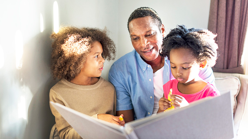 father reading to young daughters