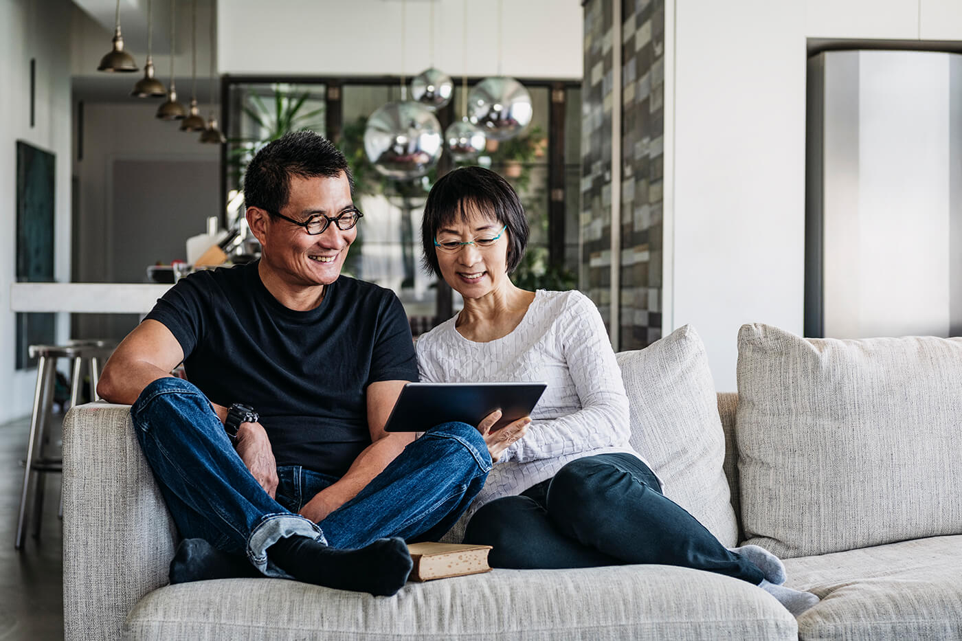 older Asian couple using tablet on the couch