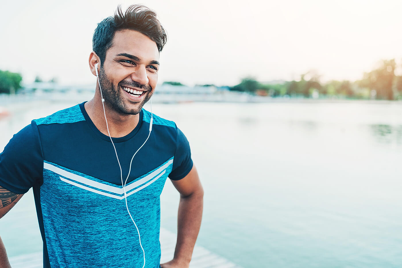 runner guy with earbuds in smiling laughing