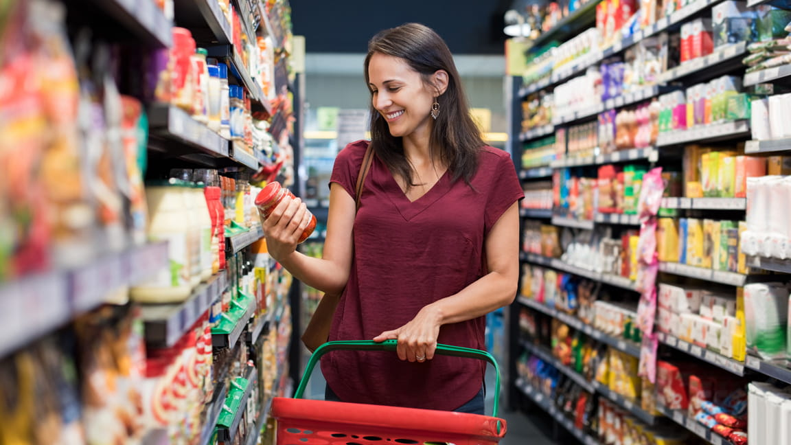 Caucasian woman reading food label in grocery store isle
