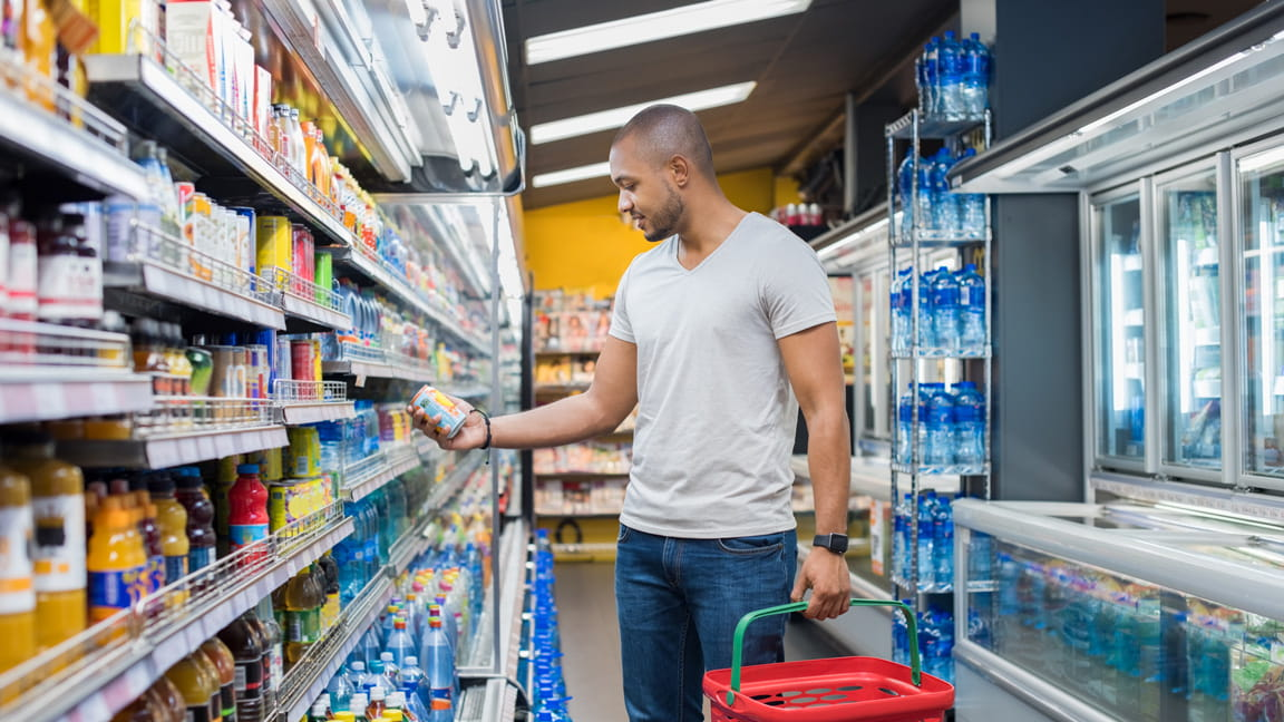 African American man grocery shopping and reading label