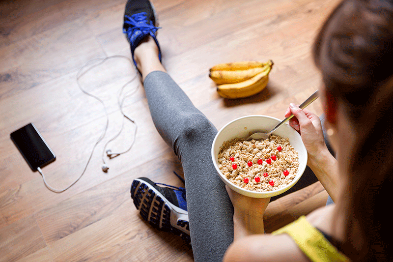 woman eating oatmeal and banana after workout