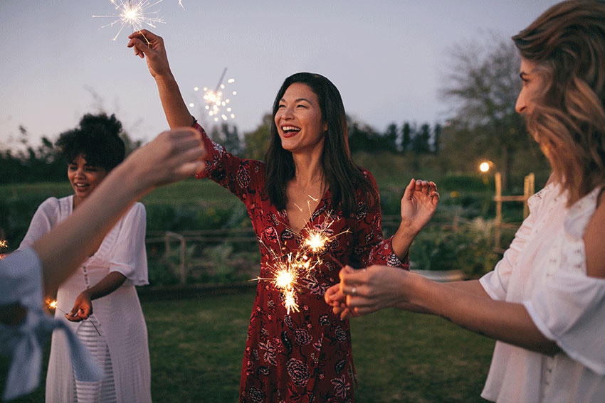happy friends playing with sparklers outdoors