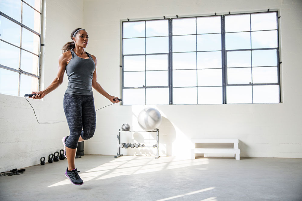 Athletic woman jumping rope at gym