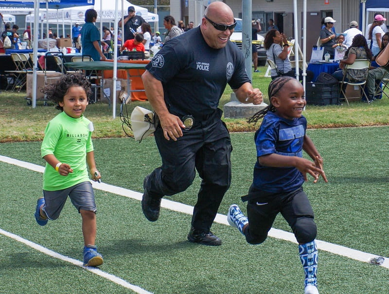 LAPD officer runs with children at Harvard Recreation Center in South Los Angeles