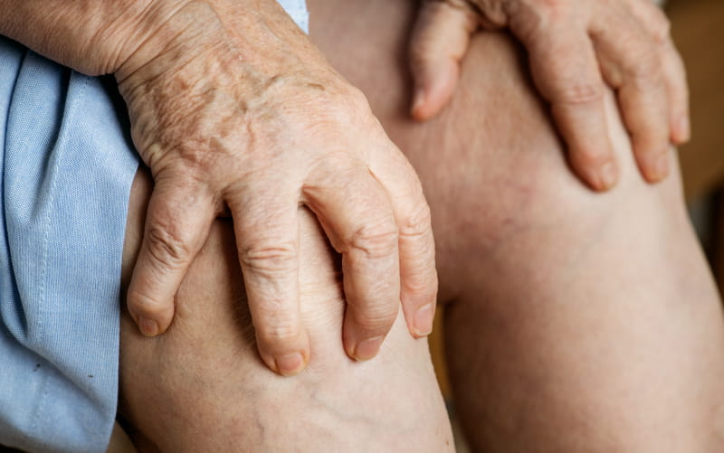 Elderly woman with knee pain (Rawpixel)