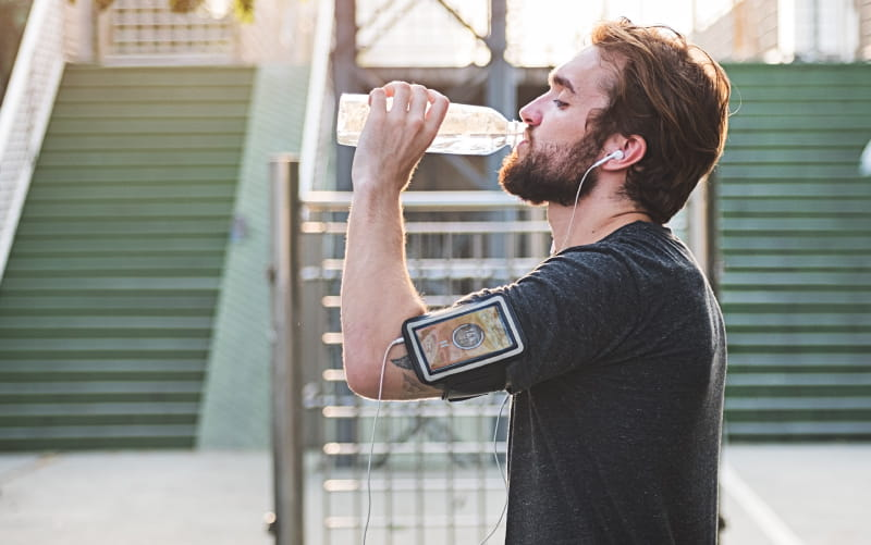 Man exercising and drinking water. (Rawpixel)