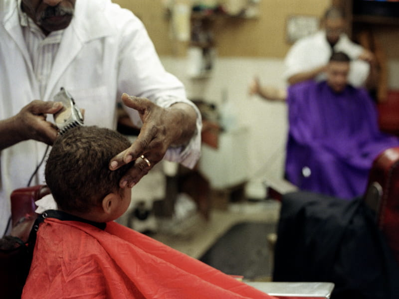 African-American barbers cutting hair.