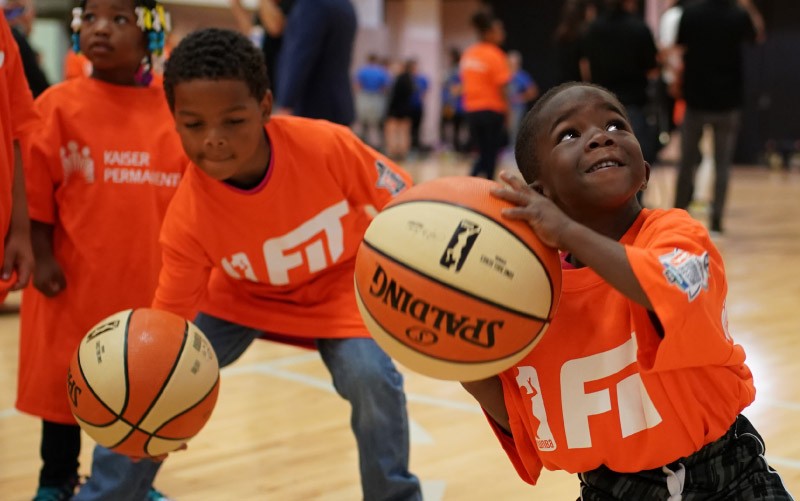 A young boy prepares to shoot a hoop at one of the WNBA's All-Star Fit Clinics. (Photo courtesy of the WNBA)