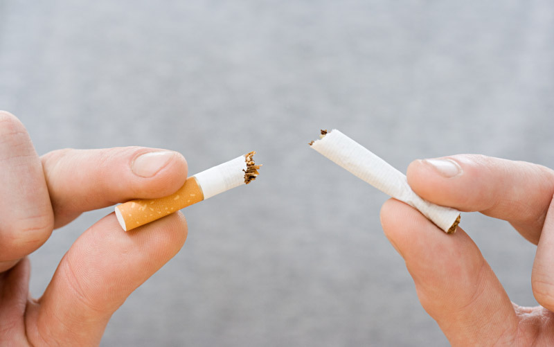 Hands breaking apart cigarette. (Image Source)