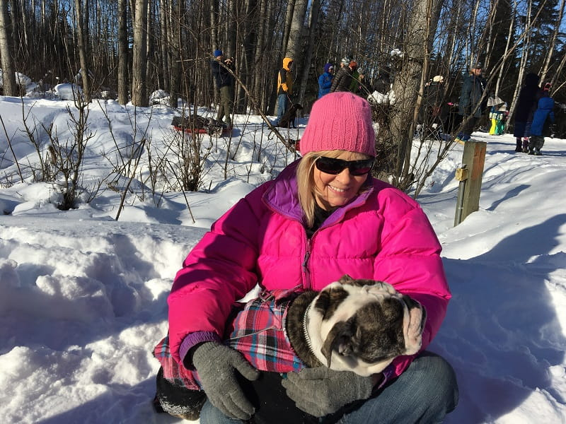 Sue Gaston holds a friendly pup she met while watching the 2017 Iditarod race through her neighborhood in Anchorage, Alaska, after she had a heart attack. (Photo courtesy of Sue Gaston)