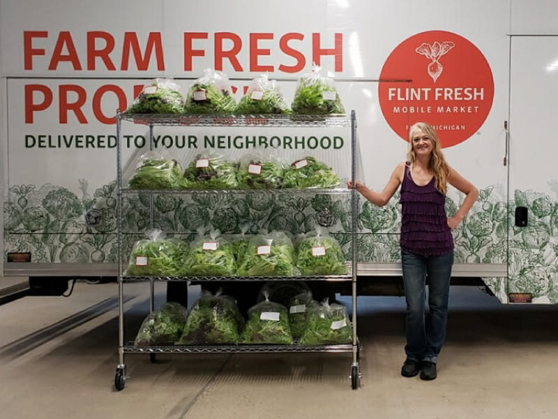 A Flint Fresh employee shows off some of the produce delivered by the organization's mobile market truck.