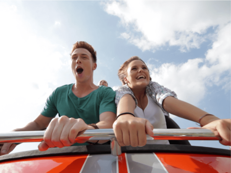 People riding roller coaster.