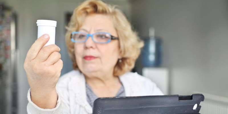 Woman with iPad looking at medication bottle