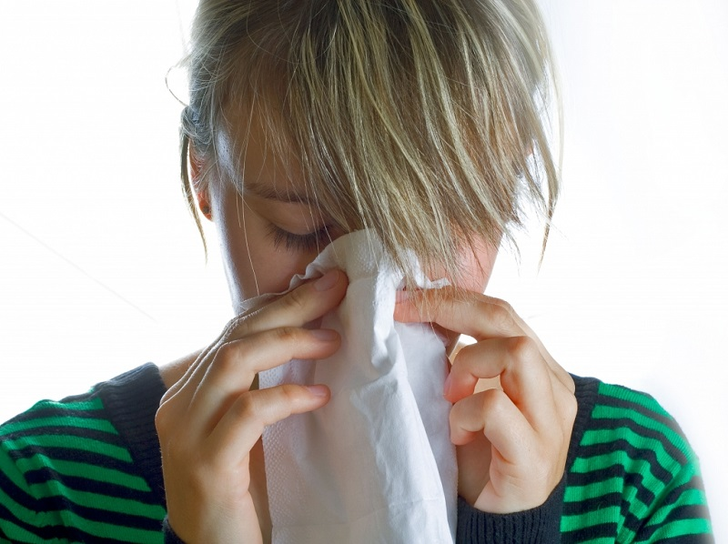 woman blowing her nose flu