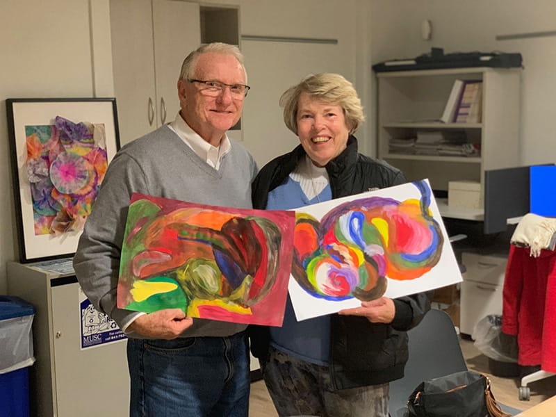 Suzie Hankins (right) and her husband Dan with their artwork from a 'Strokes for Strokes' workshop. Suzie has aphasia after surviving a stroke in 2000 and enjoys participating in the workshops with Dan. (Photo by Sarah Pack, MUSC)