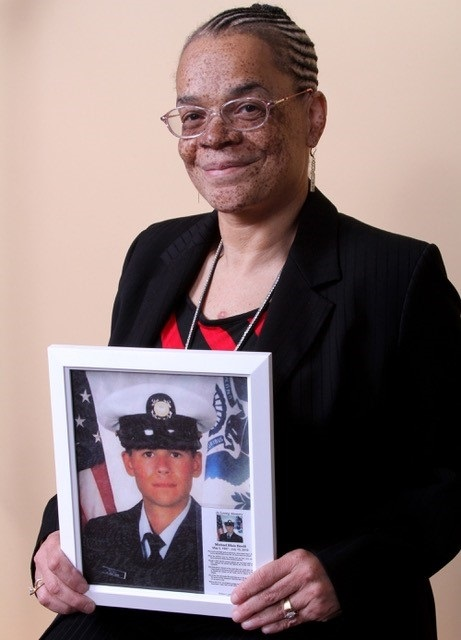 Heart transplant recipient Roxanne Watson, holding a photo of her heart donor, Michael Bovill.