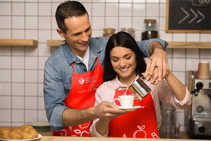 male and female couple modeling A H A branded apron