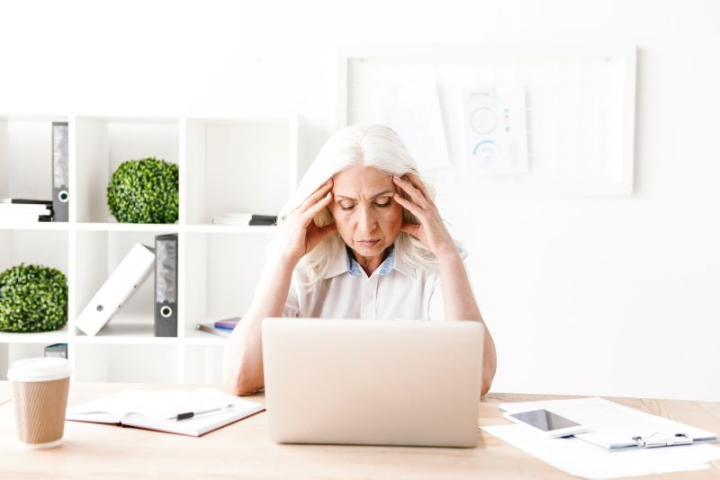 confused woman sitting in front of a laptop