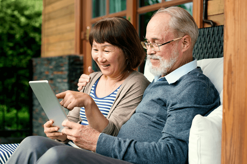 Senior Couple Talking and looking at a tablet