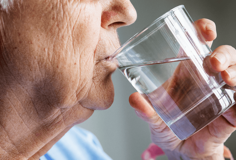 woman swallowing water from a glass