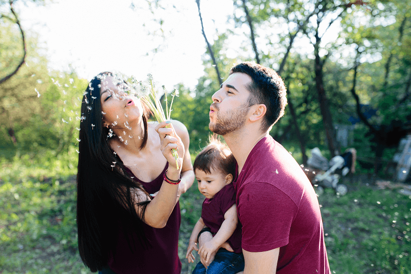 Young family and Mother is blowing flowers in the air