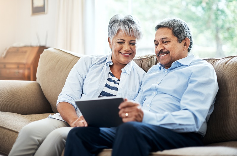 Couple on sofa looking at a tablet
