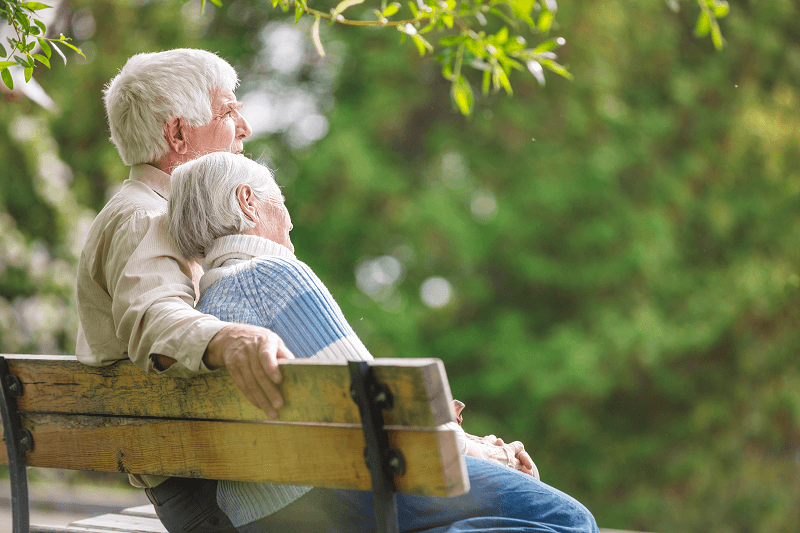 Elderly couple on a bench in a park setting