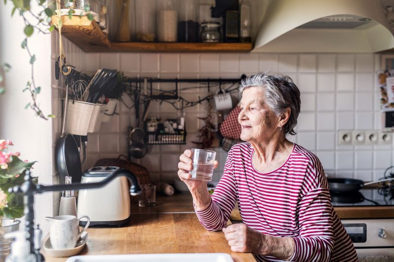 Elderly woman holding a glass of water