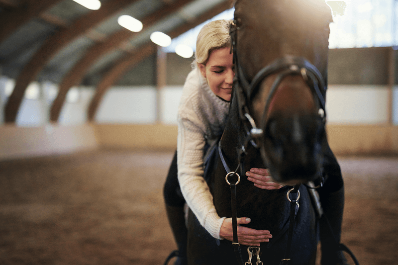 Blond woman astride horse, leaning forward hugging its neck