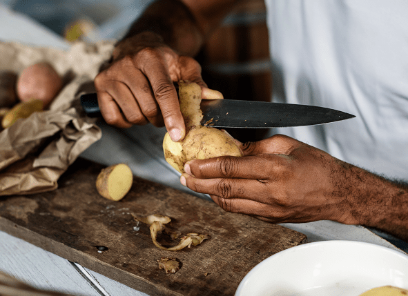 Close up of a man peeling potatoes