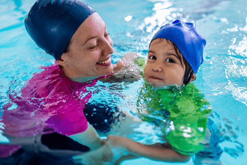 Child in swimming class with adult