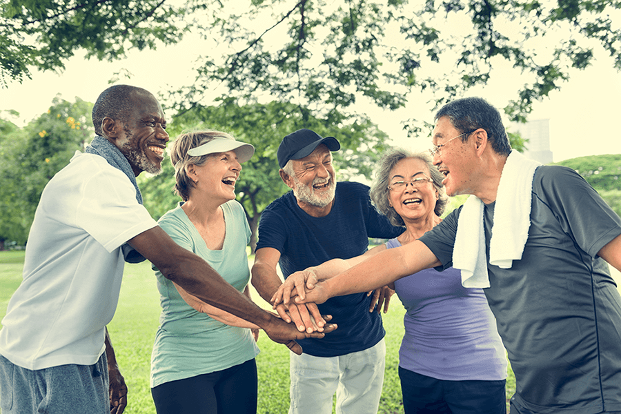 Group of senior retirement friends exercising outdoors
