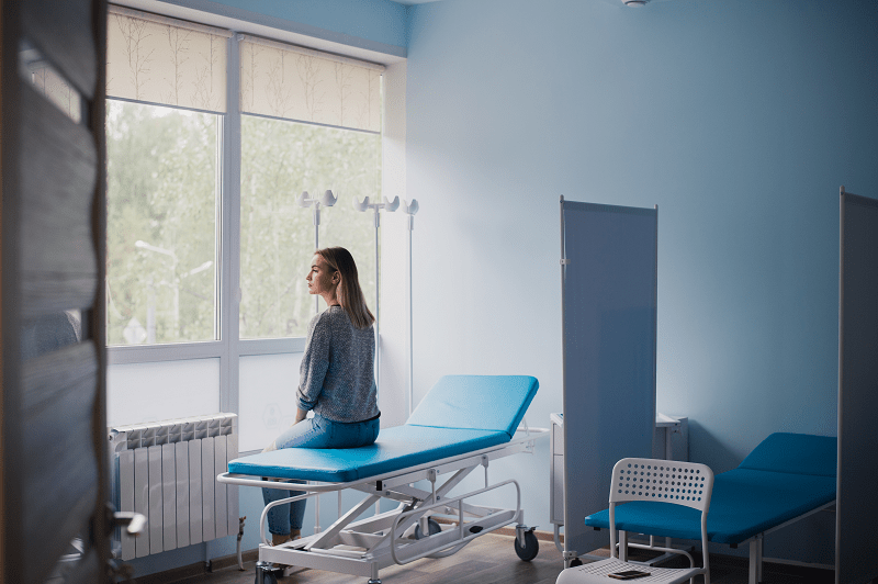 Woman waiting to be seen in a hospital room
