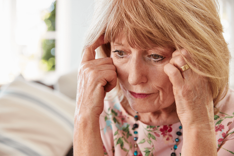 Senior Woman sitting at home with her head in her hands